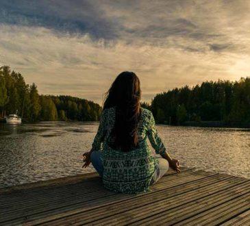 asana, joga nad jeziorem - kobieta siedząca po turecku